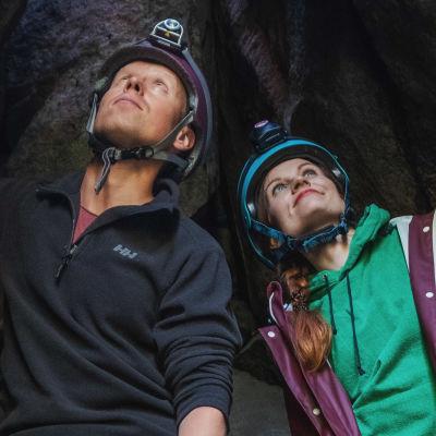 Man och kvinna i hjälm och pannlampa står i en grottöppning och tittar uppåt. Ovanför dem finns en öppning, varifrån det sipprar dagsljus.