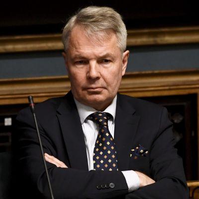 Pekka Haavisto sitter på en stol med armarna i kors. Han tittar åt sidan och ser bekymrad ut.