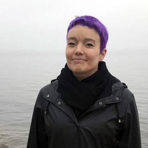 Karoliina Luoto seisoo kalliolla meren rannalla.