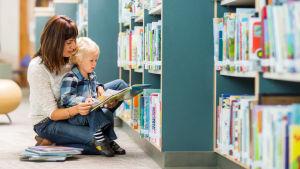 en vuxen hjälper till att läsa med ett barn i ett bibliotek