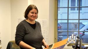 Camilla Kronqvist i sitt arbetsrum, håller i en plansch.