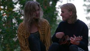Rakel ja Loviisa istuvat mökin katolla, Loviisa soittaa ukulelea ohjelmassa 24 tuntia Euroopassa