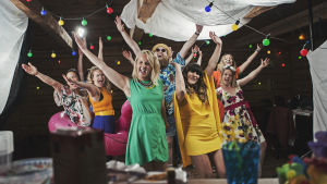 Behind the scenes bild från inspelningarna av X3M:s sommarplåga Åhi ån. X3M:s gäng står i en festlokal och viftar glatt med armarna.