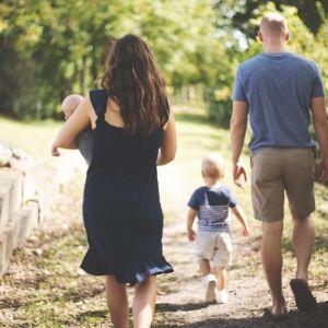 Mamma, pappa och två barn promenerar i en park.