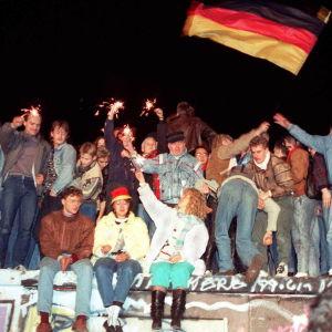 Ihmiset juhlivat Berliinin muurilla.