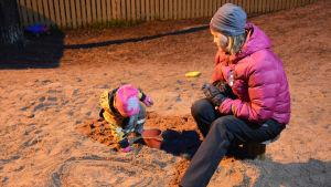 Ett litet barn leker i en sandlåda. Bredvid barnet sitter en kvinna i rosa jacka och ser på. Det är mörkt ute men sandlådan lyses upp av gårdens lampor.