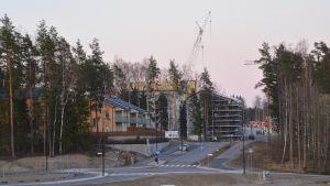 Vy från Söderkulla där manser en stor lyftkran och ett halvfärdigt höghus på en kulle.