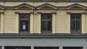 Bild utifrån på Roy Andersson som står i ett av fönstren i huset där hans studio finns.