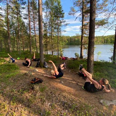 Människor gör gymparörelser i skogen.