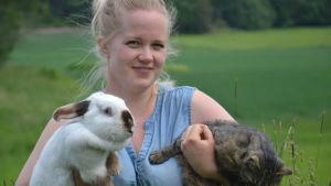 Johanna Johansson håller i en kanin och en katt.