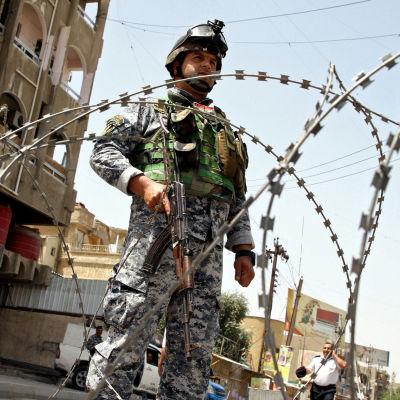 En polis står vakt under den första valdagen i Irak.