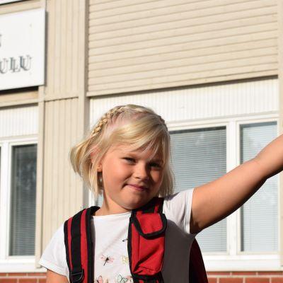 tyttö nojaa tolppaan koulun pihalla