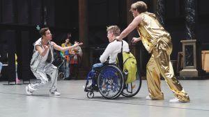Några ungdomar skuffar en rullstol på scenen i musikalen Prinsessa Ruusunen - paluu tulevaisuuteen.