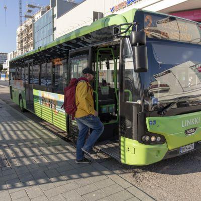 Mies nousee bussiin Jyväskylän paikallisliikenneterminaalissa.