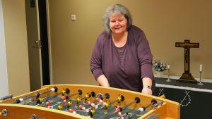 En kvinna med grått hår och lila tröja spelar ett fotbollsspel. Hon tittar in i kameran och ler. Bakom henne syns ett bord med ett kors på.