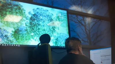 En skärm med ECDC:s logo och virusbilder och en person i förgrunden som arbetar vid en dator.