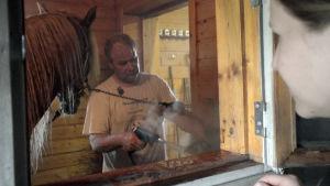 Jouko Tarvainen hevossaunassa kastelemassa saunavihtaa.