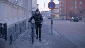 Jesse Puljujärvi leder sin cykel i Uleåborg, januari 2020.