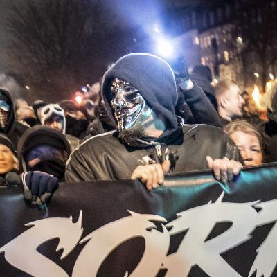 Fyra personer, två av dem maskerade, håller en stor banderoll. Den är svart med vit text. Bakom dem ser man flera människor stå.