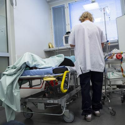 En sjukskötare sätter dropp i en patient som ligger i en säng.