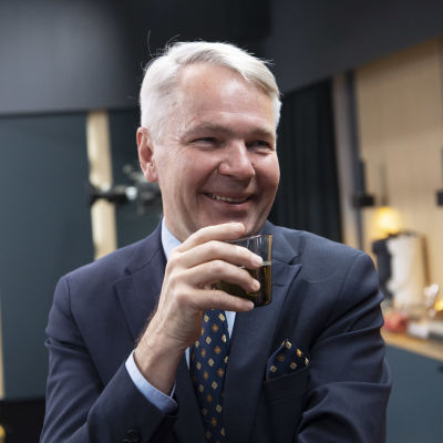 Leende man i kostym i förgrunden. Utrikesminister Pekka Haavisto (Gröna) dricker kaffe.