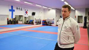 En man i vit skjorta står inne i en idrottshall. På väggen finns speglar samt Finlands och Koreas flagga. Golvet är rödblå gummimatta.