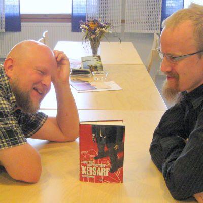 Kaksi miestä pöyrän ääressä kirjan äärellä