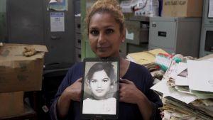 Kvinna håller upp ett foto av sig själv som barn
