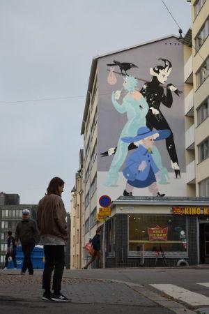 En man står på gatan framför en husgavel som han har målat ett konstverk på.
