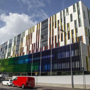 Färgrann fasad på en stor vit sjukhusbyggnad.