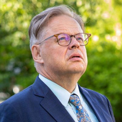 En man med grått hår och glasögon är svängd åt sidan och tittar uppåt mot himlen.