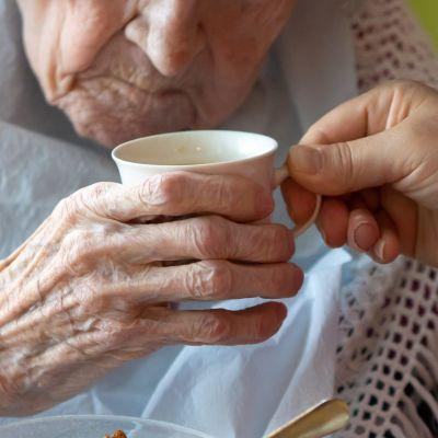 Närvårdare hjälper äldre person att äta.