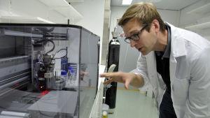 Niklas Sandler bredvid en 3D-printer.