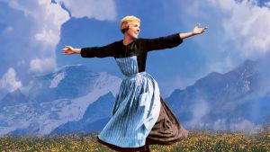 Maria (Julie Andrews) slår ut med armarna och ler uppe på ett berg.