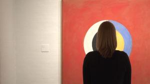 en museibesökare står framför ett verk av Hilma af Klint
