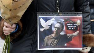 En kvinna håller i en blombukett och bär en bild på en man på sin jacka.