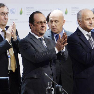 Ranskan presidentti Francois Hollande (kuvassa keskellä) ja maan ulkoministeri Laurent Fabius (oikealla)taputtavat käsiään ilmastosopimuksen julkistamisen jälkeen Pariisissa 12. joulukuuta.