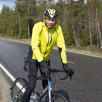Heikki Mäkelä pyörän kanssa maantiellä.