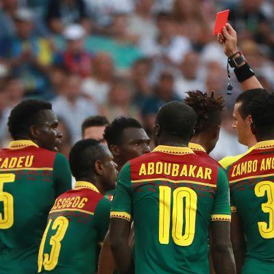 Erotuomari Wilmar Roldán nostaa punaisen kortin Kamerunin pelaajalle.