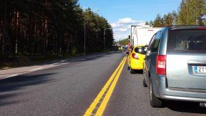 Bilar står stilla bakom varandra på en landsväg.
