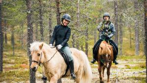 Kristiina Komulainen ratsastaa metsässä.