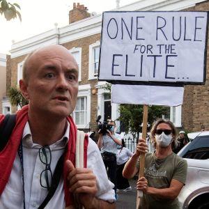 """Punaisiin liiveihin ja valkoiseen paitaan pukeutunut Cummings kulkee  kadulla laukkua kantaen. Taustalla näkyy mielenosoittaja kyltin kanssa. Mielenosoittajalla on kasvomaski. Kyltissä on teksti: One rule for the elite..."""""""