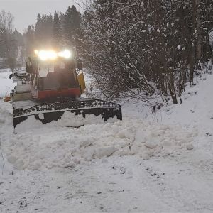 Bandtraktor plogar snö för skidspår.