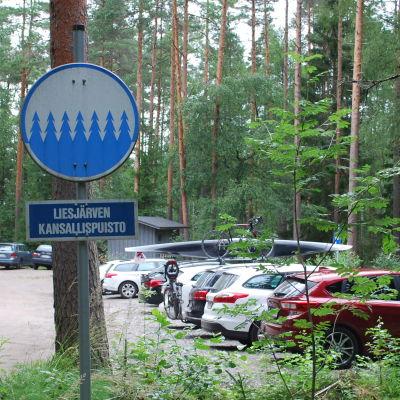 """Kansallispuiston parkkipaikalla on monta autoa sekä kyltti """"Liesjärven kansallispuisto""""."""