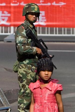 En uigurisk flicka går förbi kinesiska soldater