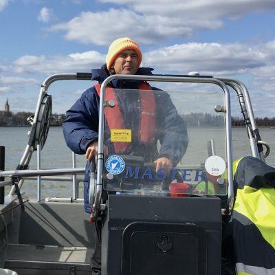 En man står och kör en båt.