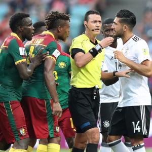 Domaren omringad av spelare i Confederations Cup