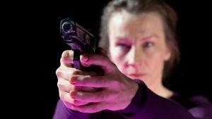 Skådespelaren Elisabet Carlsson siktar med en pistol.