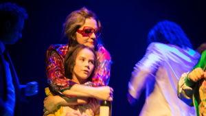 Teaterscen där en kvinna med en vinflaska i handen håller om ett barn.