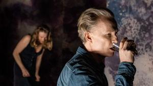 Skådespelaren Sven Ahlström dricker ur ett glas, i bakgrunden skådespelaren Elisabet Carlsson.